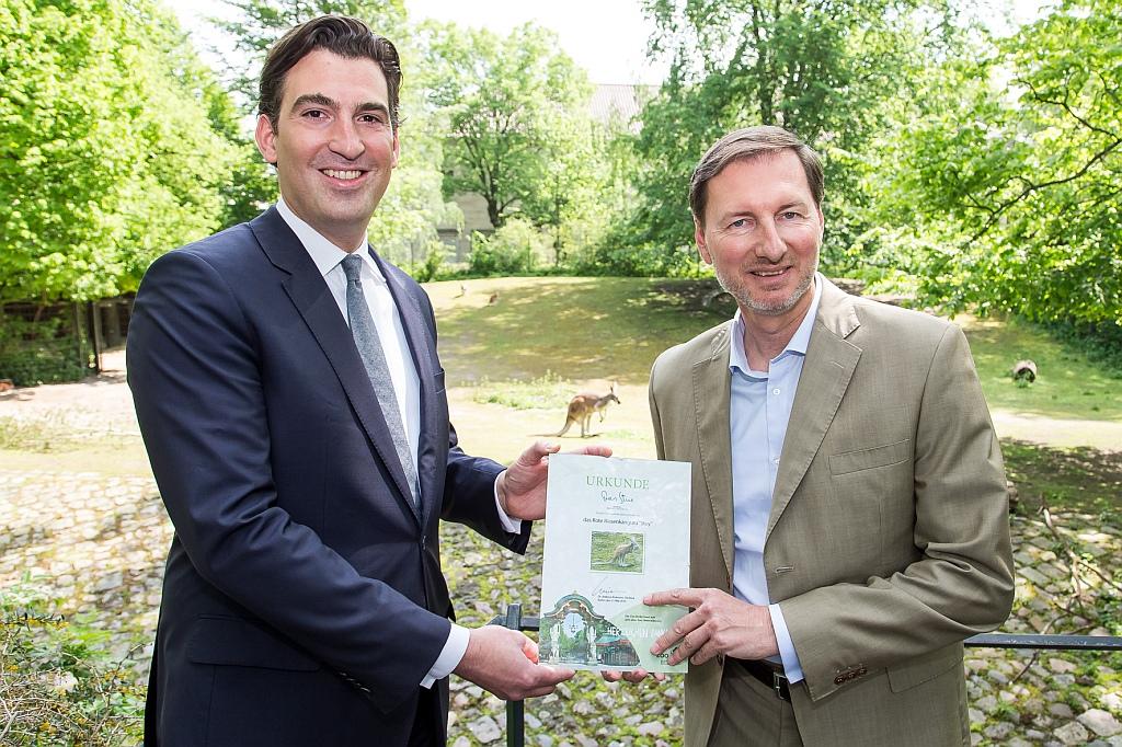 Hoteldirektor Alexander Doerr (links) übergibt Zoodirektor Andreas Knieriem die Patenschafts-Urkunde.